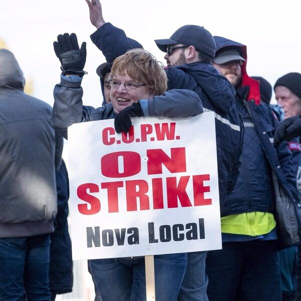 Une femme tient une affiche sur laquelle est écrit en rouge: «En grève».