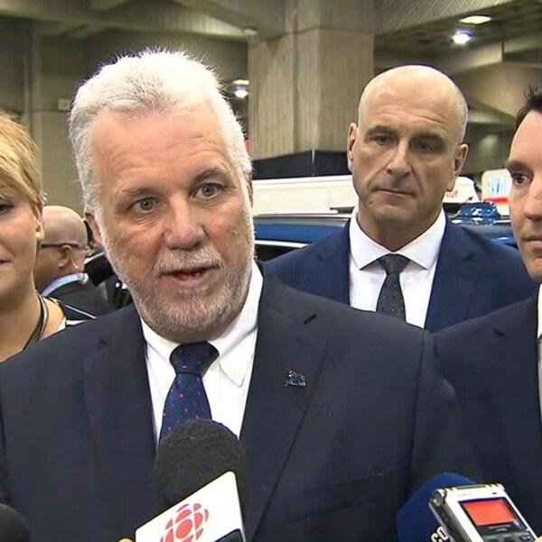 Philippe Couillard, entouré des ministres Isabelle Mélançon et André Fortin.