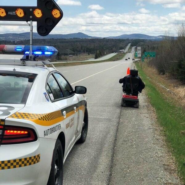 Un homme circulant sur un quadriporteur sur l'autoroute suivi par une voiture de la SQ.