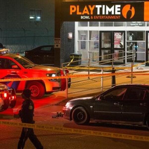 Des voitures de polices garées devant un salon de quilles à Toronto