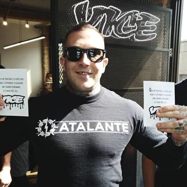 M. Lévesque, qui porte un chandail d'Atalante, pose devant le logo de Vice.