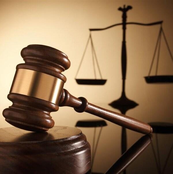 Image d'un marteau sur fond de balance, deux symboles représentant la justice.