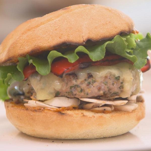 Un burger de veau avec poivrons, champignons et laitue dans une assiette.