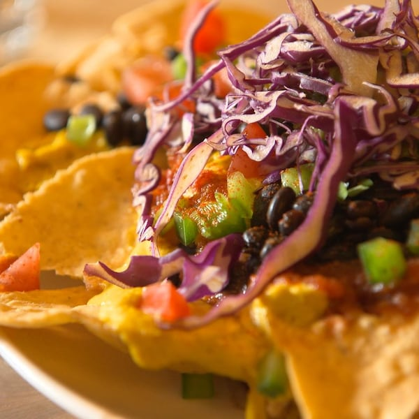 Des nachos avec une sauce aux graines de tournesol et des légumes.
