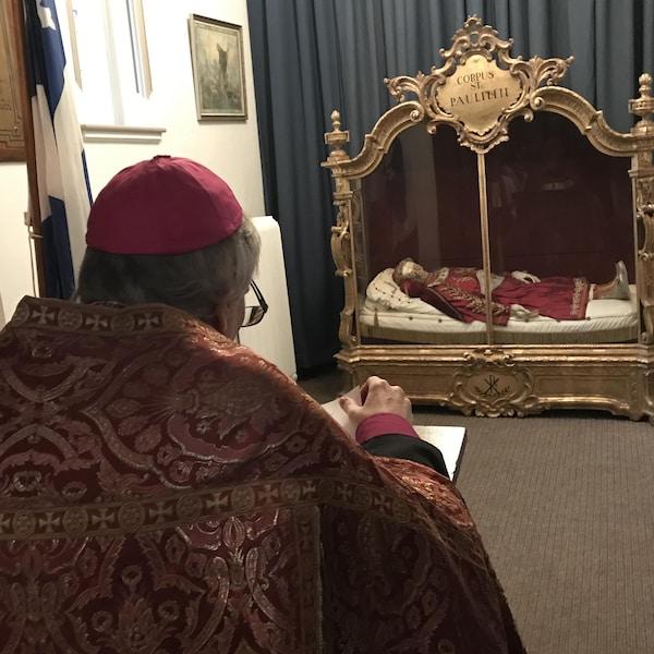 Le Dom Charles-Rafael Payeur regarde de loin la relique de Saint-Paulil.