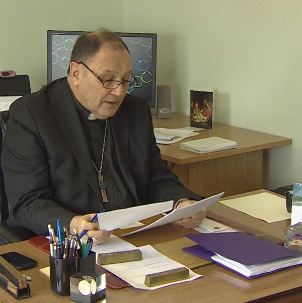 L'évêque Richard Grecco consulte des documents à son bureau.