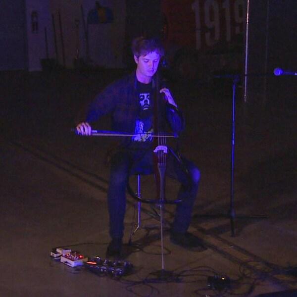 Le violoncelliste Rob Knaggs, en concert, dans une salle sombre