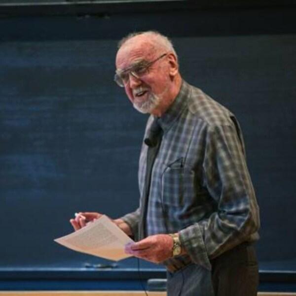 Un professeur enseigne devant un tableau noir.