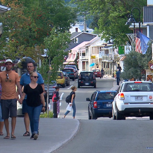 Des gens marchent le long d'une rue commerciale