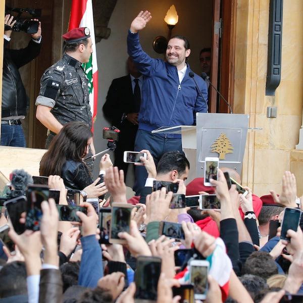 Saad Hariri, tout sourire devant des sympathisants qui brandissent leurs téléphones pour le prendre en photo.