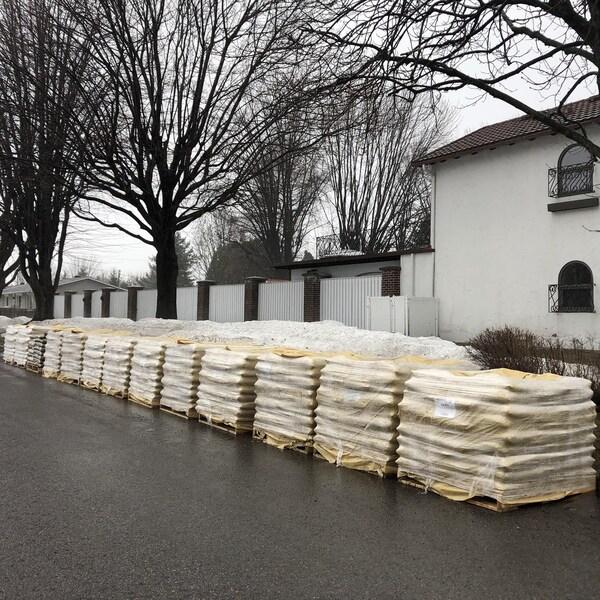 Des sacs de sable, sur des palettes de bois, déposées sans être utilisés sur une rue fantôme.