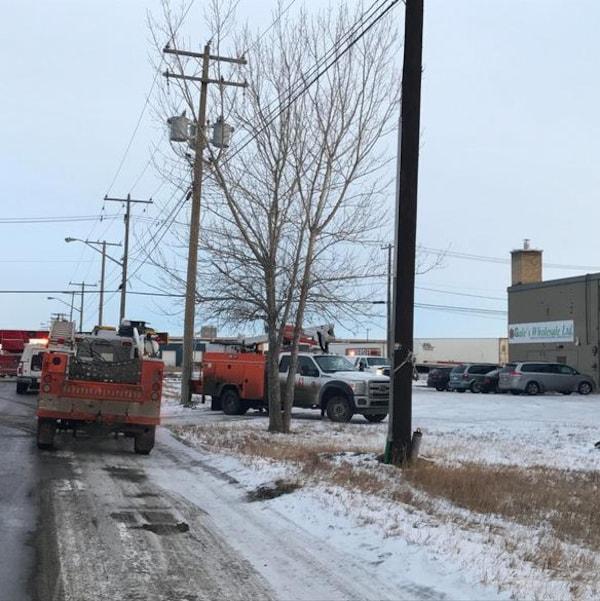 Des camions de techniciens de SaskEnergy dans une rue enneigée.