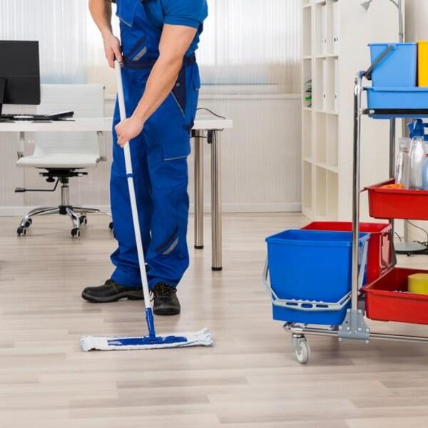 Un homme dans un uniforme de travail bleu nettoie le plancher d'un bureau avec une vadrouille.