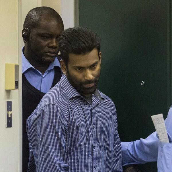 Deux policiers escortent le détenu.