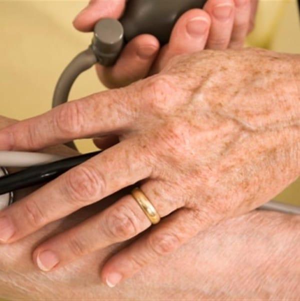 Des mains tiennent un stéthoscope dans le creux d'un coude