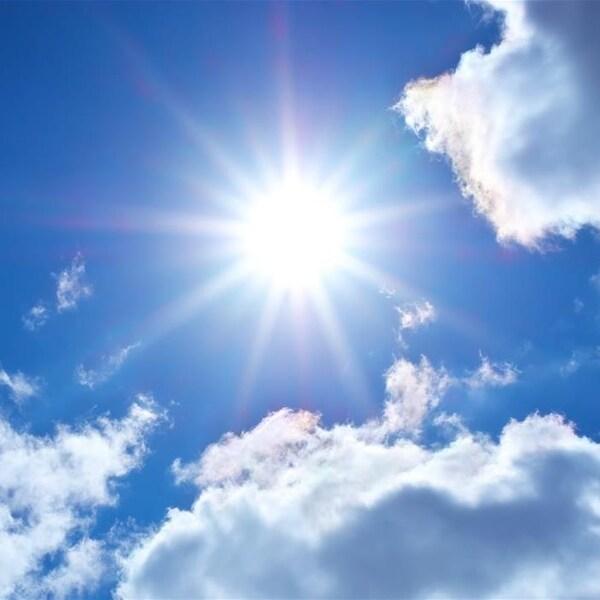 Un soleil brille entre les nuages dans un ciel bleu.