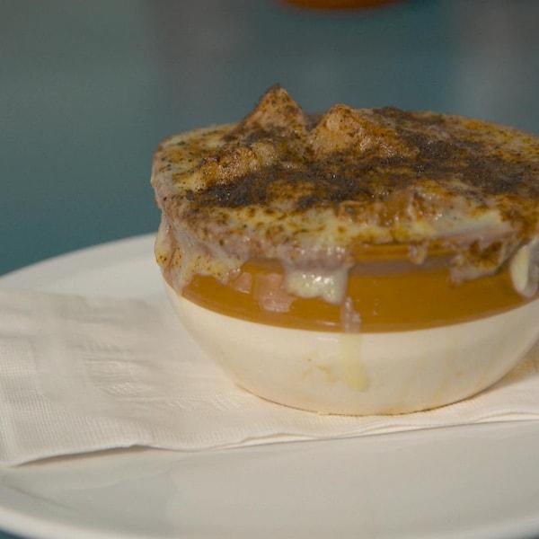Un bol de soupe à l'oignon gratinée dans une assiette.