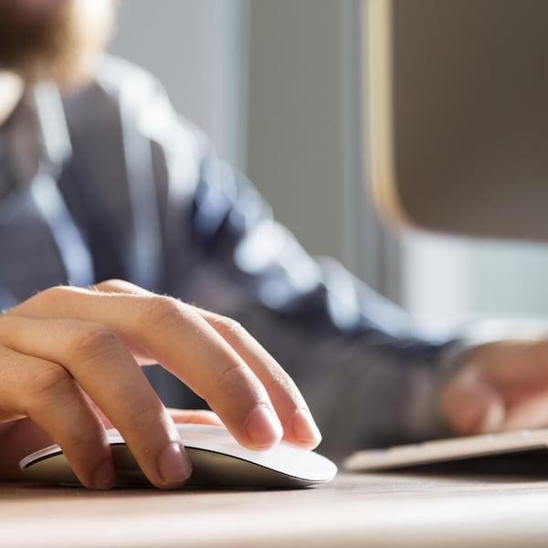 Gros plan sur la main d'un homme qui manipule une souris d'ordinateur.