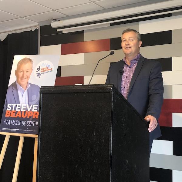 Steeve Beaupré, derrière un lutrin, fait une allocution à côté de sa pancarte électorale pour les élections municipales à Sept-Îles.
