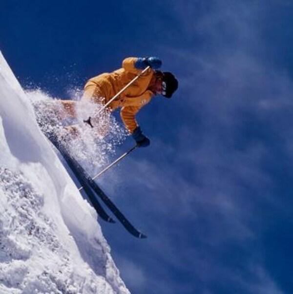 En veste jaune, Sylvain Saudan descend en ski une pente très forte, soulevant de la neige alors qu'il amorce un virage.