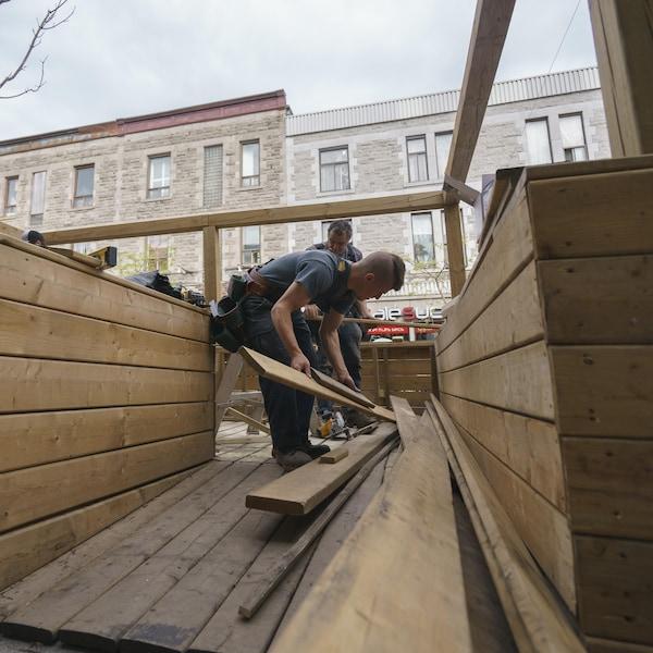Des ouvriers installent une terrasse près d'un restaurant de l'avenue du Mont-Royal.