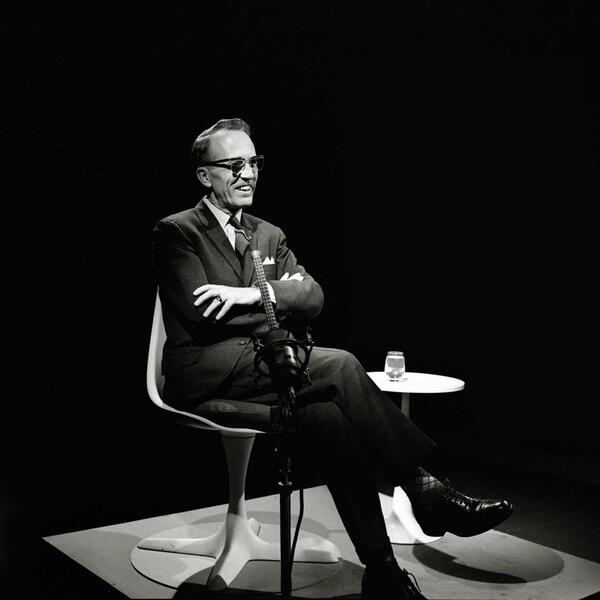 Une photo en noir et blanc d'un homme dans la cinquantaine souriant assis sur une chaise.
