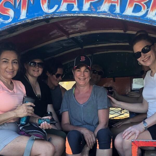 Huit femmes habilles en vêtements d'été sont assises à l'arrière d'une fourgonnette.