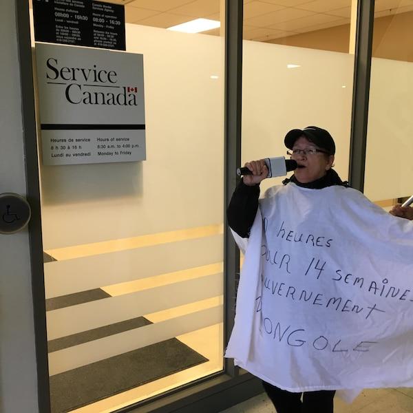 Une manifestante devant les bureaux de Services Canada.