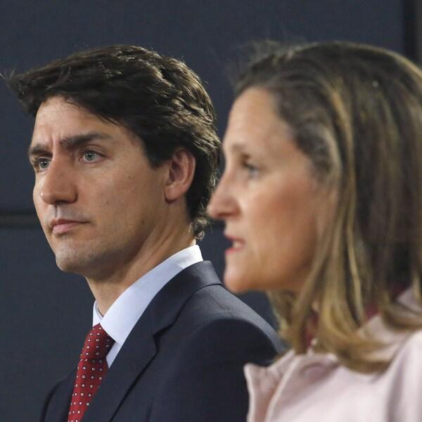 Justin Trudeau écoute Chrystia Freeland lors d'une conférence de presse