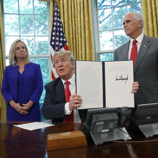 Le président américain Donald Trump signe le décret avec, derrière lui, la secrétaire à la Sécurité intérieure Kirstjen Nielsen et le vice-président Mike Pence.