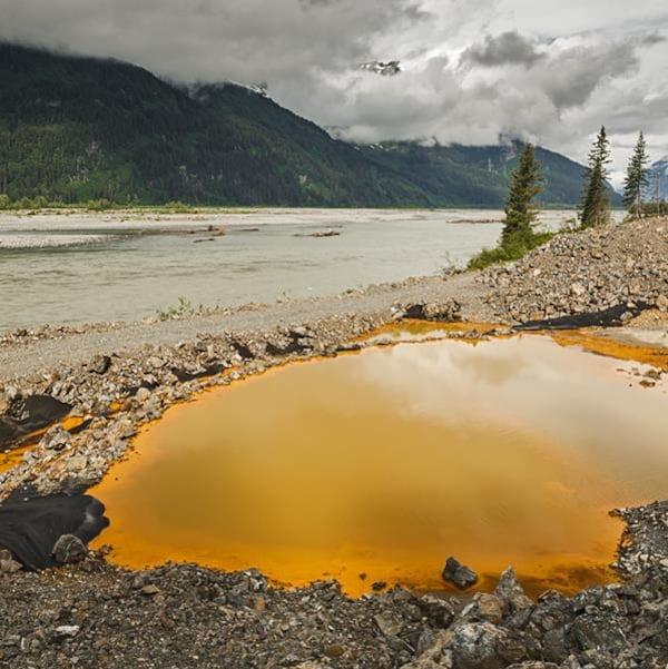 Flaque d'eau orangée sur le bord d'une rivière.