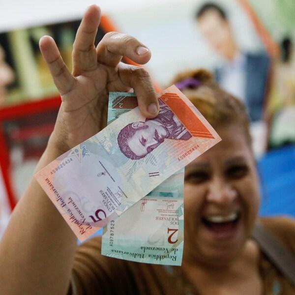 Une femme sourit en brandissant les nouveaux billets de banque du Venezuela.