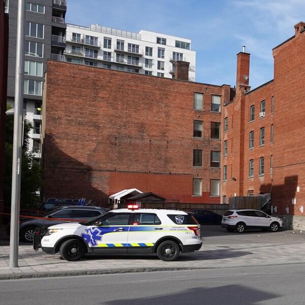 Une voiture de paramédic devant un VUS gris, dans un stationnement du sud-ouest de Montréal.