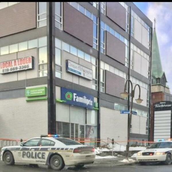 Des voitures de police se retrouvent devant la pharmacie Familiprix du 225, boulevard Saint-Joseph dans le secteur Hull à Gatineau.