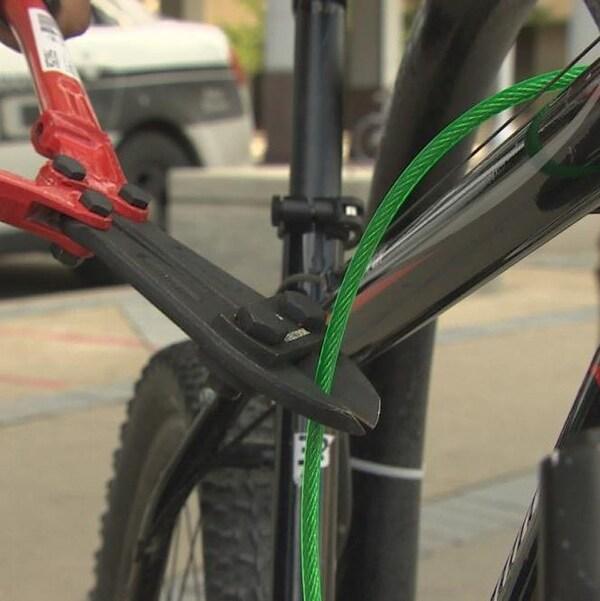 Une personne coupe un cadenas de vélo.