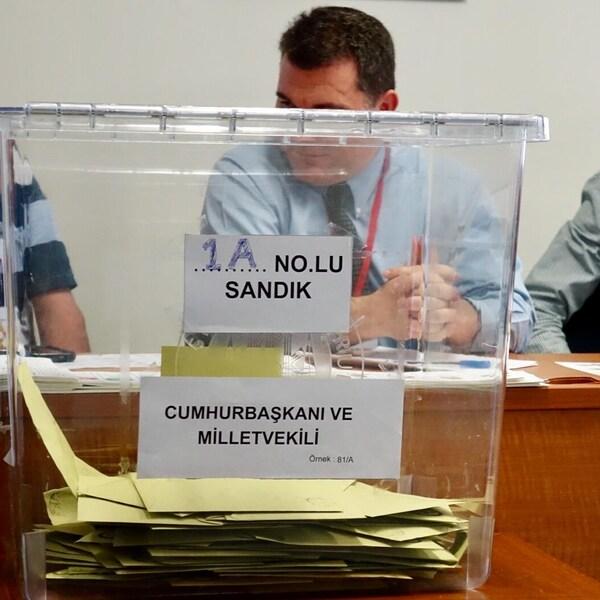 En avant-plan, une urne en plastique contenant des enveloppes empilées. En arrière-plan, des employés de l'ambassade assis derrière un bureau.