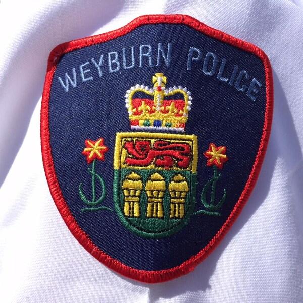 Le logo de la police de Weyburn épinglé sur un vêtement.