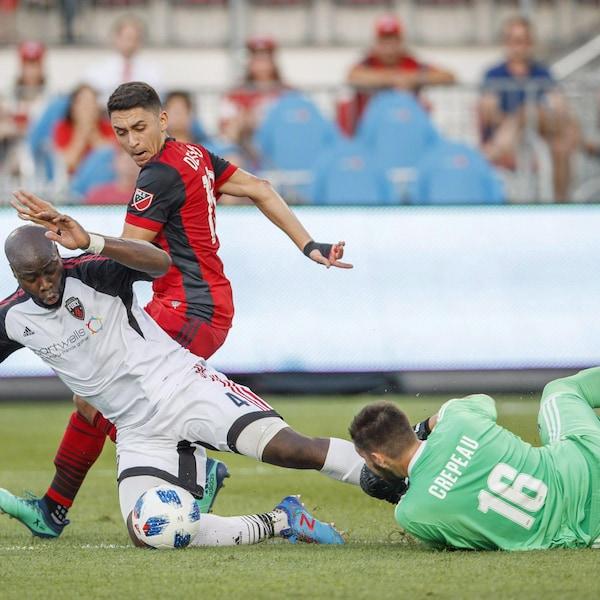 Le gardien Maxime Crépeau effectue un arrêt contre Marco Delgado du Toronto Fc pendant que son coéquipier Nana Attakora tombe sur le sol.