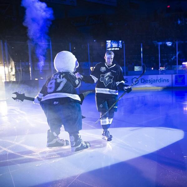 Sur la patinoire, un joueur de hockey s'approche d'une mascotte qui tient une fausse guitare, sous des lumières bleutées dans l'aréna