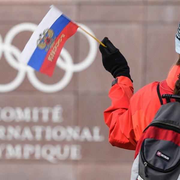 Une femme agite un drapeau de la Russie devant le quartier général du Comité international olympique, à Lausanne, en Suisse.
