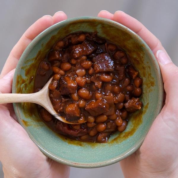 Un plat de fèves au lard dans les mains d'une femme