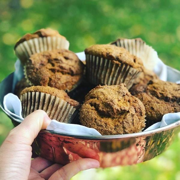 Une main tient un bol en métal rempli de muffins.