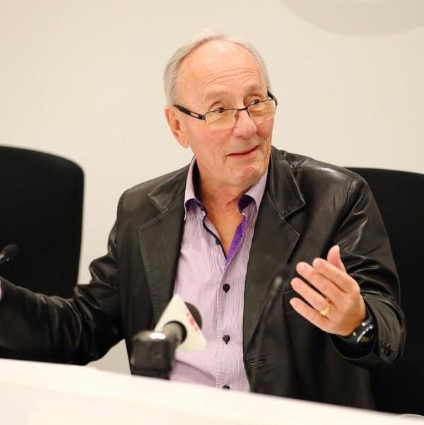 Émile Loranger, assis à la table du conseil, s'adresse aux élus.