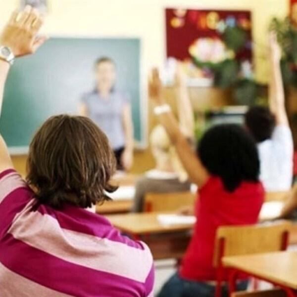 Des enfants lèvent la main dans une salle de classe
