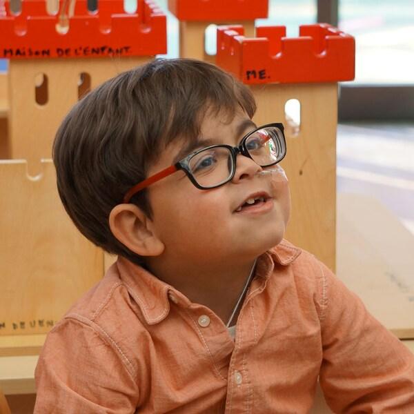 Imad, un petit garçon à lunettes, sourit devant un château fort dans <i>Et les mistrals gagnants</i>, d'Anne-Dauphine Julliand