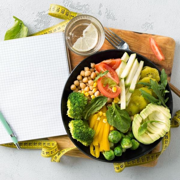 Une assiette remplie de légumes, avec un calepin de notes et un ruban à mesurer.