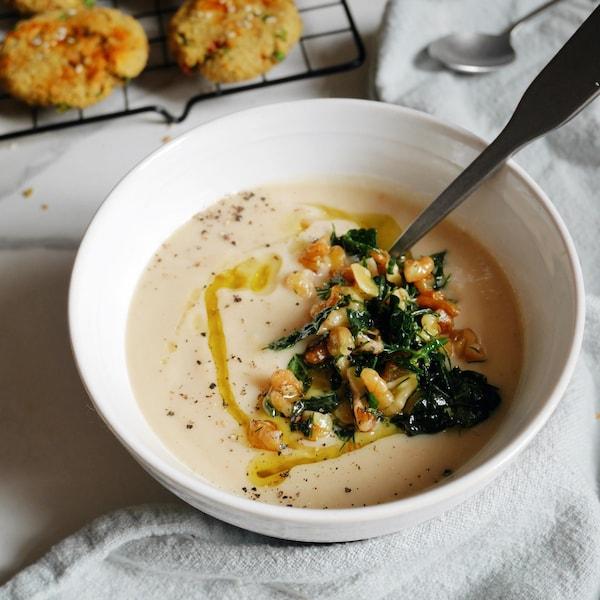 Une soupe garnie de noix et aneth servie dans un bol.