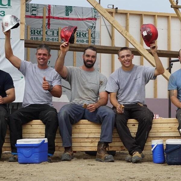 Cinq travailleurs de la construction lèvent leur chapeau en souriant.