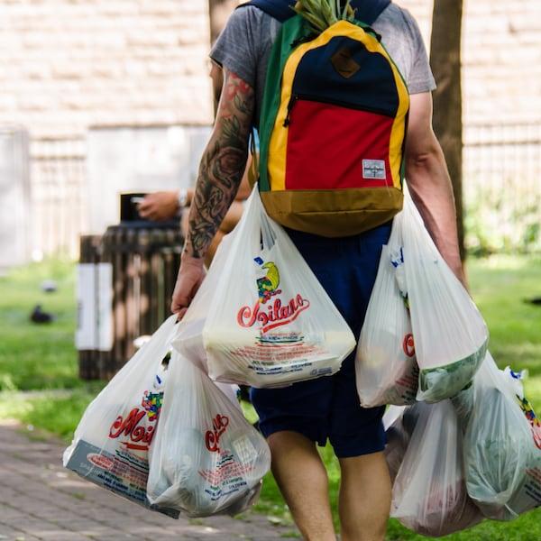 Un homme transporte au moins sept sacs d'emplettes en plastique