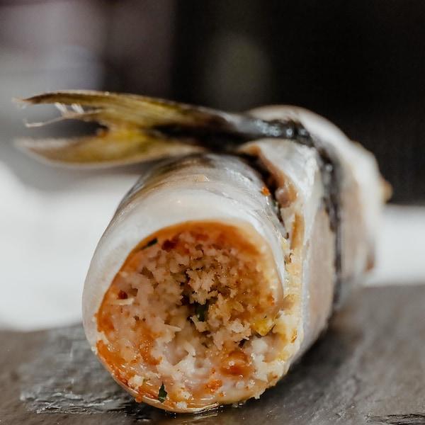Un rouleau de poisson disposé sur une planche de pierre.